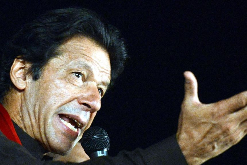 Pakistani former cricketer-turned politician Imran Khan addresses supporters during a sit-in protest against government in front of the Parliament in Islamabad on Oct 21, 2014. A Pakistani anti-terrorism court has issued arrest warrants for Mr K