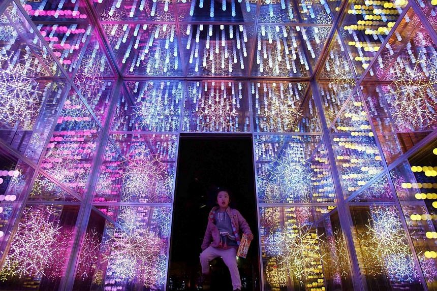 A girl looking at Christmas decorations outside Tokyo Dome in Tokyo on Nov 7, 2014. -- PHOTO: REUTERS