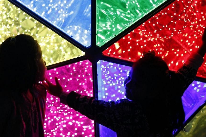 Children looking at a Christmas decoration outside Tokyo Dome in Tokyo on Nov 7, 2014. -- PHOTO: REUTERS