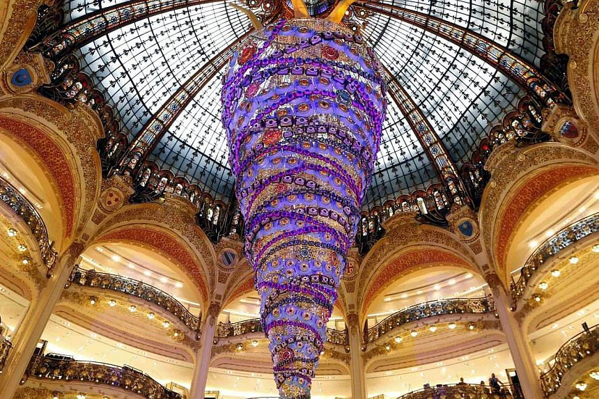 A giant Christmas tree installed upside down in the middle of the Galeries Lafayette department store in Paris ahead of the holiday season in the French capital on Nov 6, 2014. -- PHOTO: REUTERS