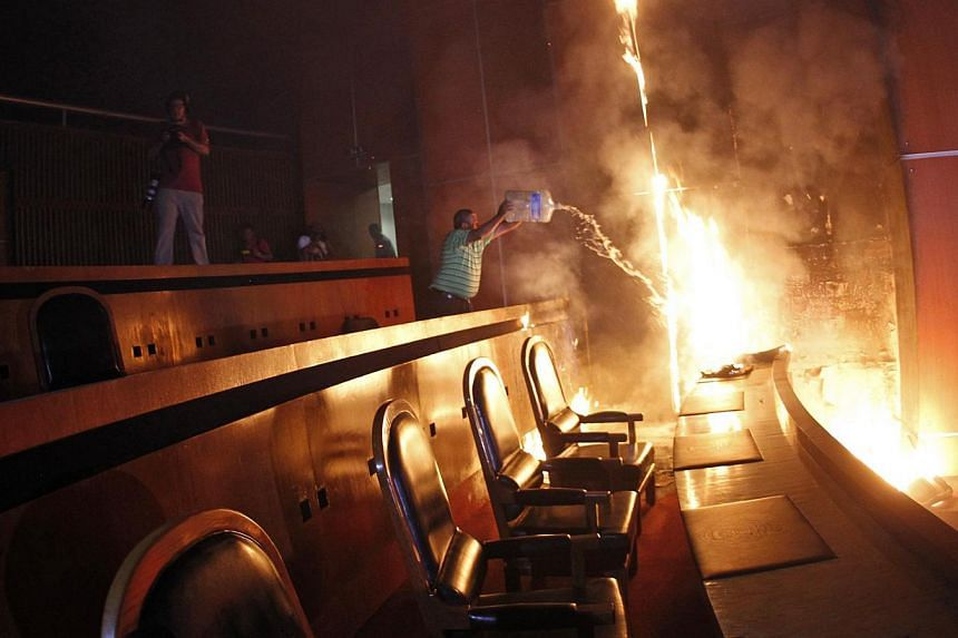 A man tries to extinguish a fire set alight at the principal hall of the City Congress by members of CETEG (State Coordinator of Teachers of Guerrero teacher's union), in Chilpancingo on Nov 12, 2014. -- PHOTO: REUTERS