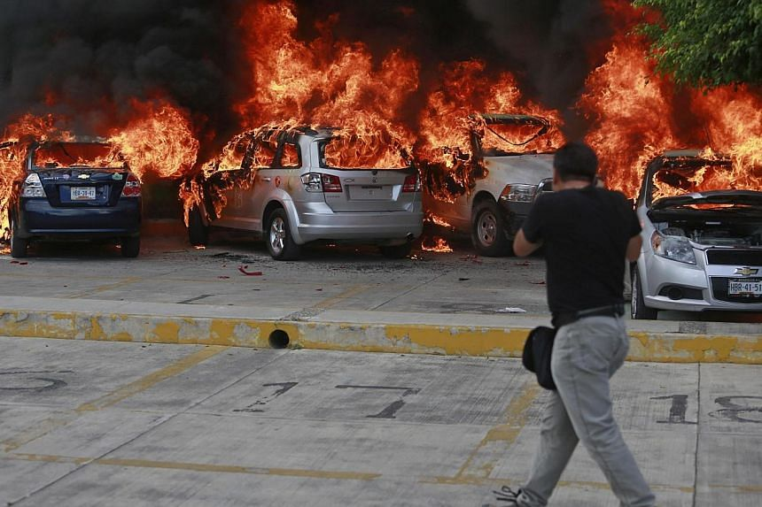 A news photographer take pictures of cars set alight by CETEG (State Coordinator of Teachers of Guerrero teacher's union) members at a City Congress parking lot in Chilpancingo on Nov 12, 2014. -- PHOTO: REUTERS