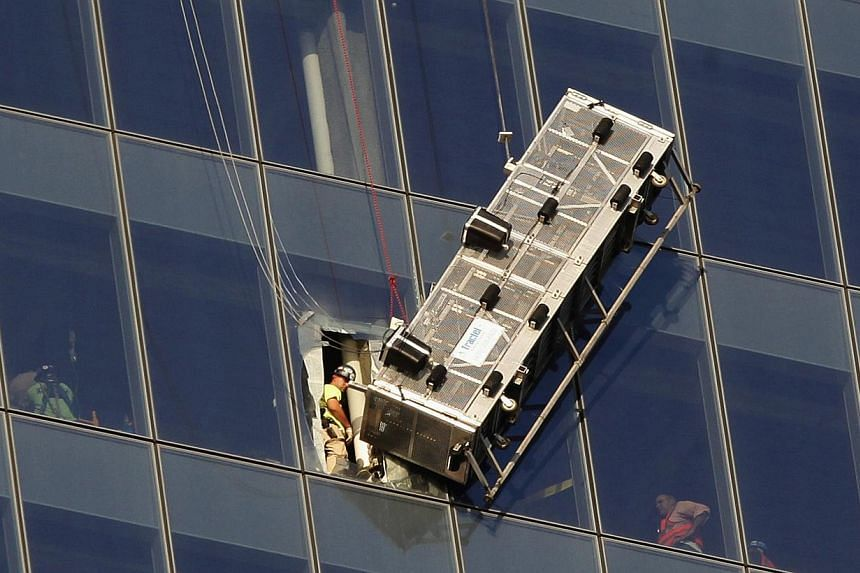 Workers look out at a broken scaffolding that had stranded window washers earlier on the side of 1 World Trade Center in New York on Nov 12, 2014. -- PHOTO: REUTERS
