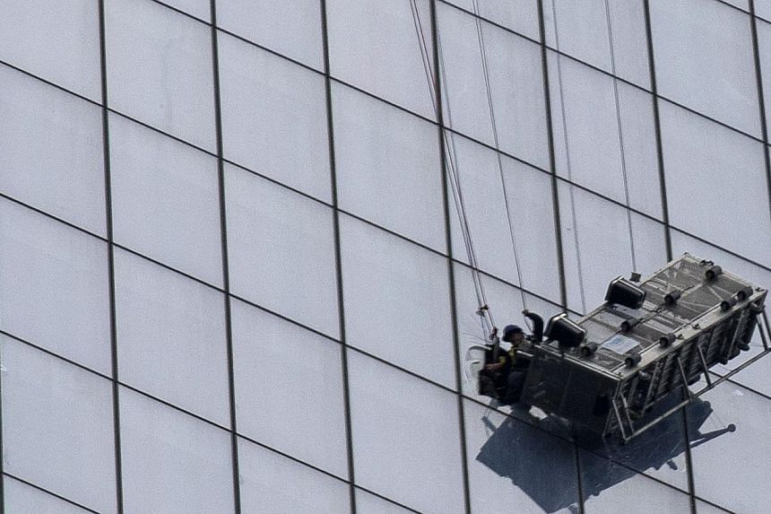 A stranded window washer is pulled into 1 World Trade Center in New York on Nov 12, 2014. -- PHOTO: REUTERS