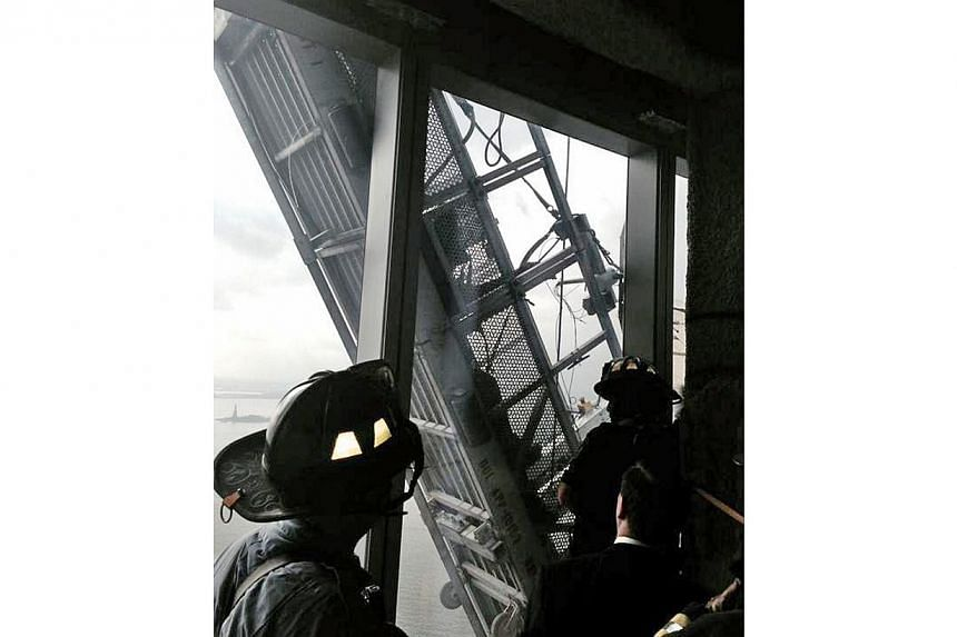 A picture tweeted by the New York City Fire Department appears to show workers trapped on scaffolding outside 1 World Trade Center in New York on Nov 12, 2014. -- PHOTO: REUTERS