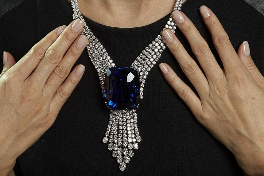 A Christie's staff member wears the Blue Belle of Asia, a 392.52-carat sapphire, during an auction preview in Geneva on Nov 6, 2014. -- PHOTO: REUTERS