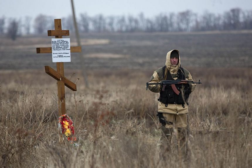A pro-Russian gunman stands guard as Dutch investigators (unseen) arrive near parts of the Malaysia Airlines Flight MH17 at the crash site near the Grabove village in eastern Ukraine on Nov 11 2014. -- PHOTO: AFP