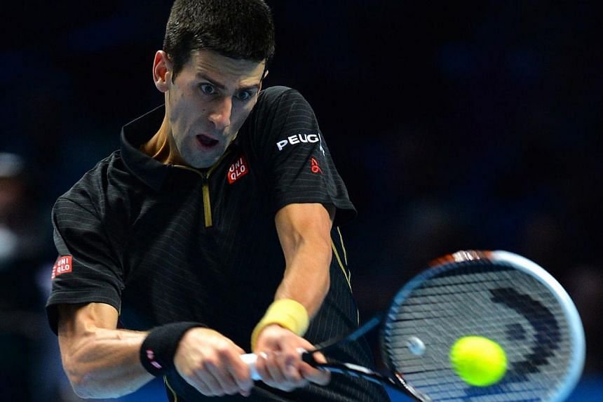 Novak Djokovic of Serbia returns the ball to Stan Wawrinka of Switzerland during their tennis match at the ATP World Tour finals at the O2 Arena in London on Nov 12, 2014. -- PHOTO: REUTERS