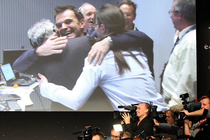 Journalists film near a giant screen featuring European Space Agency scientists celebrating after the announcement of the first-ever landing on a comet, done by European probe Philae, at theESA/ESOC in Darmstadt, western Germany, on Nov 12, 2014. --
