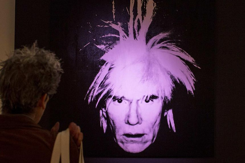 A man examines Self-Portrait by Andy Warhol during a media preview at Christie's auction house in New York. -- PHOTO: REUTERS