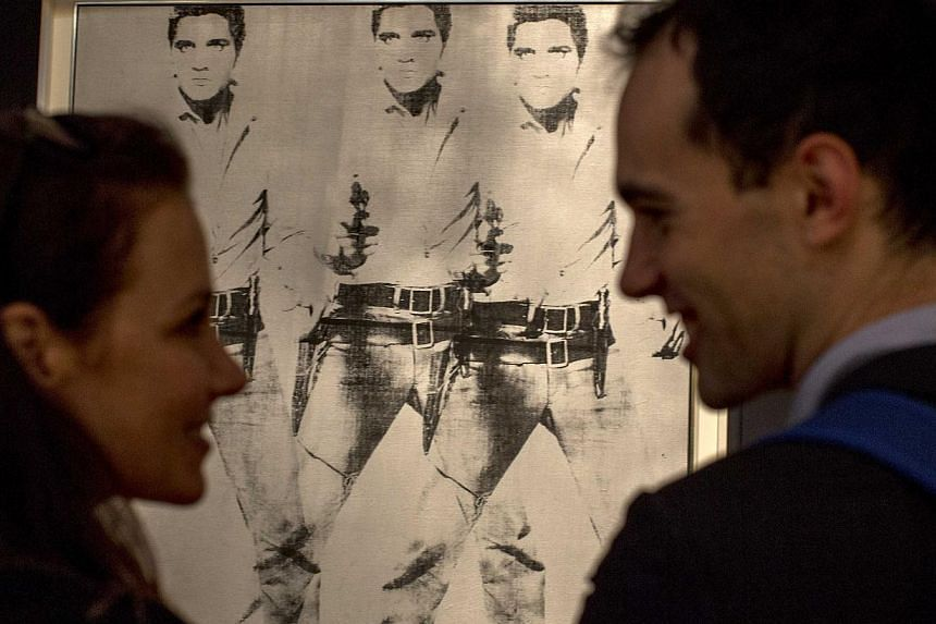 """A couple talk in front of """"Triple Elvis"""" by Andy Warhol during a media preview at Christie's auction house in New York. -- PHOTO: REUTERS"""