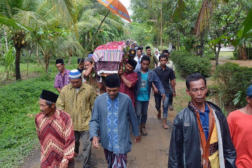Relatives and villagers carry the coffin of Sumarti Ningsih, one of two Indonesian women allegedly murdered by British banker Rurik Jutting in Hong Kong, during her funeral at Gandrungmangu village, in Cilacap, Central Java province, on Nov 12, 2014.