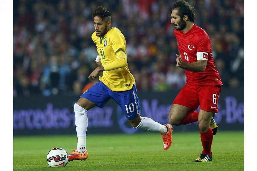 Hamit Altintop of Turkey (right) challenges Neymar of Brazil during their international friendly match at Sukru Saracoglu stadium in Istanbul on Nov 12, 2014. -- PHOTO: REUTERS