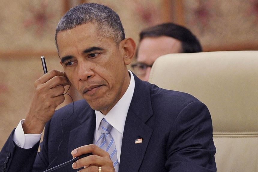 US President Barack Obama adjusts his earpiece during the ASEAN-US Summit at the Myanmar International Convention Center in Myanmar's capital Naypyidaw in this file photograph. He will hold talks with Myanmar's democracy icon Aung San Suu Kyi. -- PHO