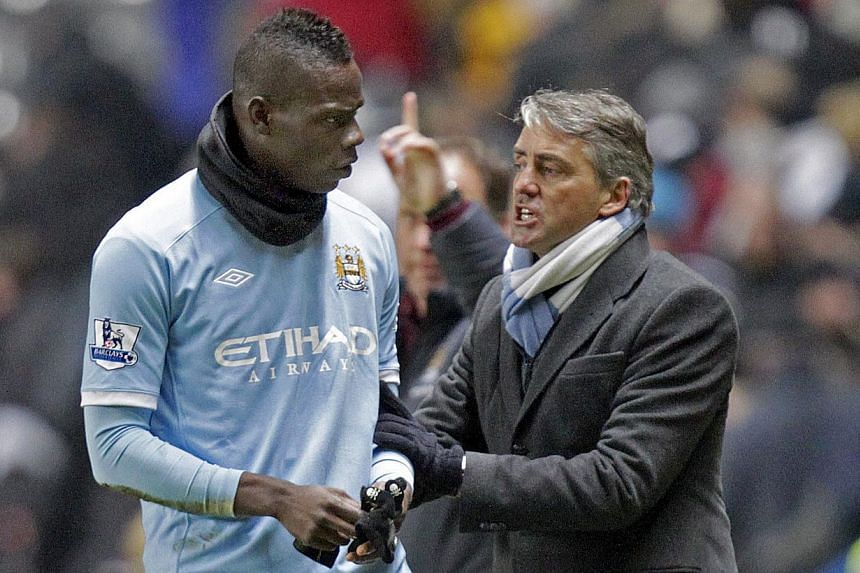 Manchester City's Italian manager Roberto Mancini (right) pushes Italian striker Mario Balotelli back onto the pitch after their 3-1 win in the English Premier League football match against Newcastle United at St James' Park, Newcastle-Upon-Tyne, nor
