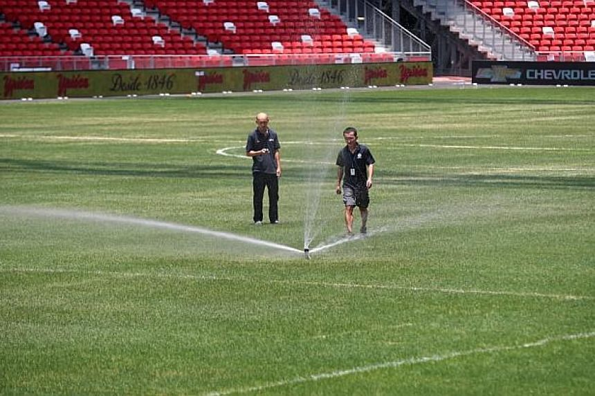 Workers tending to the pitch at the National Stadium.-- PHOTO: THE NEW PAPER FILE
