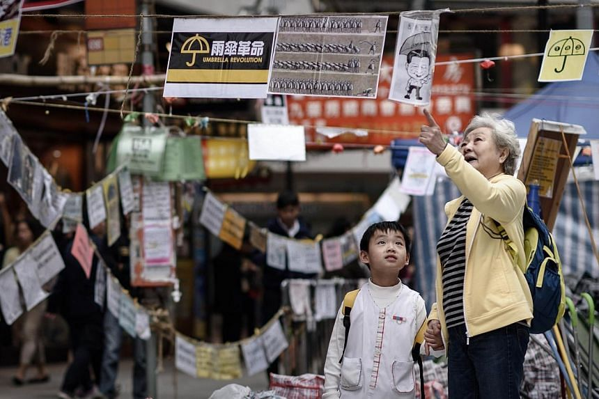 """A elderly woman explains to a child the meaning of posters set up by pro-democracy protesters at a protest site in the Causeway Bay district of Hong Kong on Nov 14, 2014.Hong Kong warned Friday that """"encouraging"""" growth in the third quarter may"""