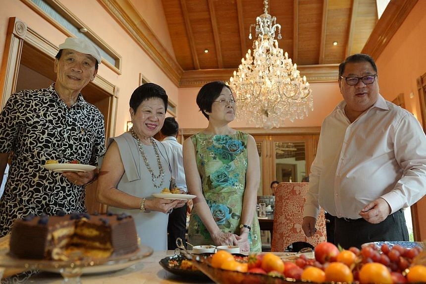 Tangs chairman Tang Wee Sung (right) hosting a tea for his former employees (from left) Charlie Ong, Lucy Lee and Dinah Tan at his Bukit Timah home yesterday. The long-serving employees were each presented with a pewter plaque and a lifetime Tangs di