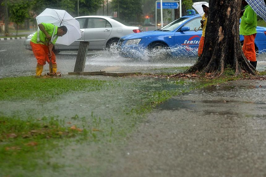 Workers clearing dead leaves and rubbish from drainage holes which caused a pool of water to collect at the junction of Ang Mo Kio Avenue 3 and Ang Mo Kio Street 23 on the afternoon of Nov 13, 2014. -- ST PHOTO: KUA CHEE SIONG