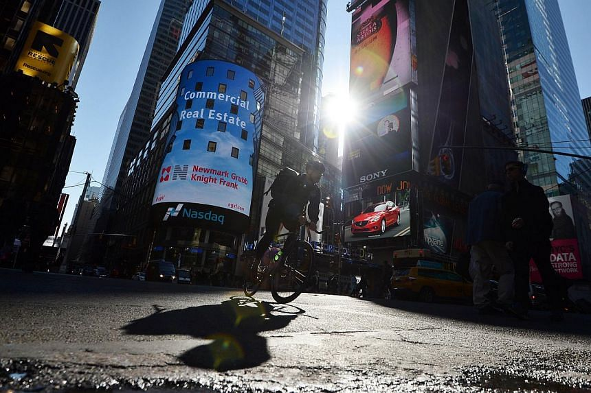 A man rides his bike through Times Square as electronic billboards advertising various products flash around him in New York on Nov 3, 2014. -- PHOTO: AFP