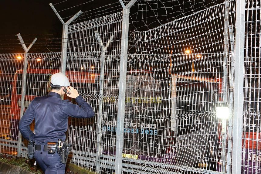 A Lianhe Zaobao reporter at the scene saw that a slit large enough for a person to enter was cut open in the metal mesh fence. -- PHOTO: LIANHE ZAOBAO