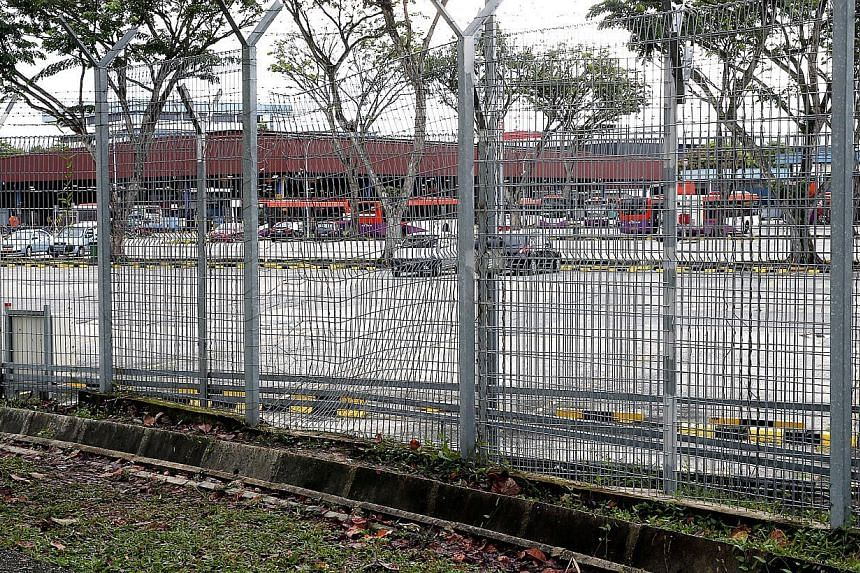 The fence around an Ang Mo Kio bus depot was found cut on Thursday night, and an intruder is suspected to have entered the facility. -- ST PHOTO: LAU FOOK KONG