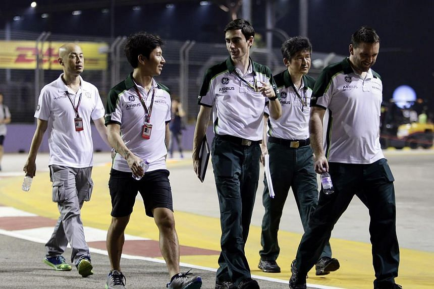 Caterham Formula One driver Kamui Kobayashi (second left) of Japan and crew members walk on the the Marina Bay street circuit ahead of the Singapore F1 Grand Prix in Singapore Sept 18, 2014. The struggling Caterham team are set to return to action in