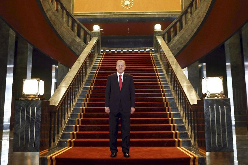 Turkish President Recep Tayyip Erdogan poses inside the new Ak Saray presidential palace (White Palace) on the outskirts of Ankara on Oct 29, 2014. Erdogan is planning to expand his already controversial new presidential palace with a 250-room r