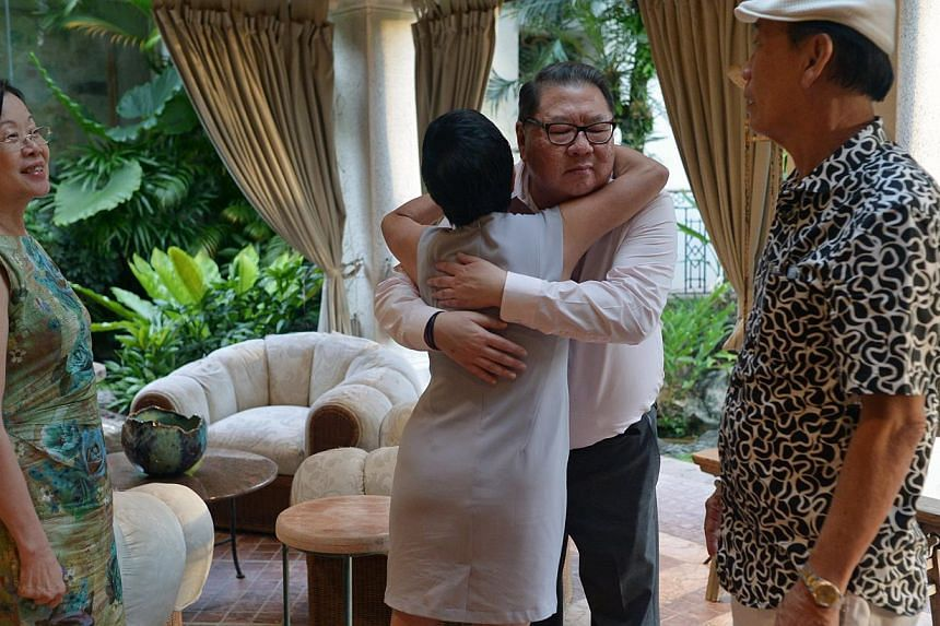 Ms Lucy Lee gives Mr Tang Wee Sung, chairman of Tangs, a hug before leaving his home. With them are, Ms Dinah Tan (left) and Mr Charlie Ong (right). -- ST PHOTO: CAROLINE CHIA
