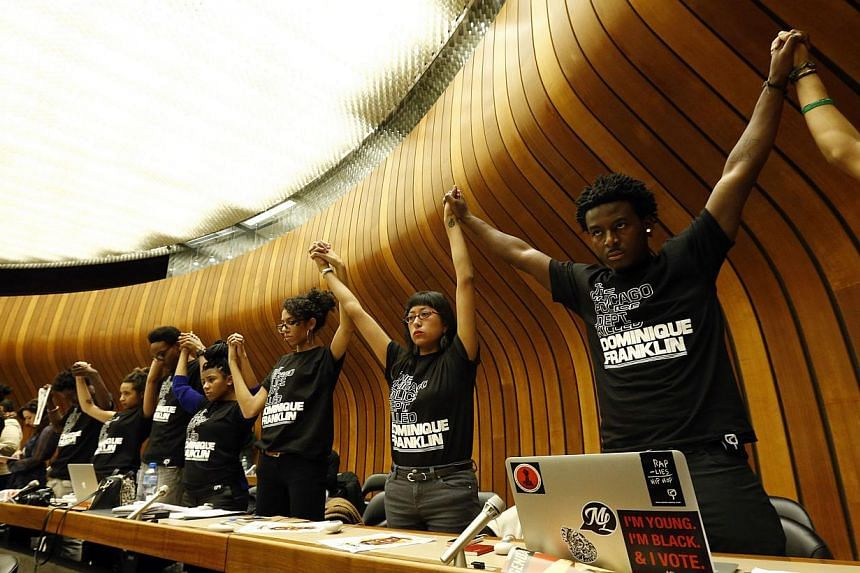 """Activists hold hands during a silent protest at a hearing of the United States at the Committee against Torture at the United Nations in Geneva Nov 13, 2014. The activists wore T-shirts with the slogan: """"The Chicago Police Dept killed Dominique Frank"""