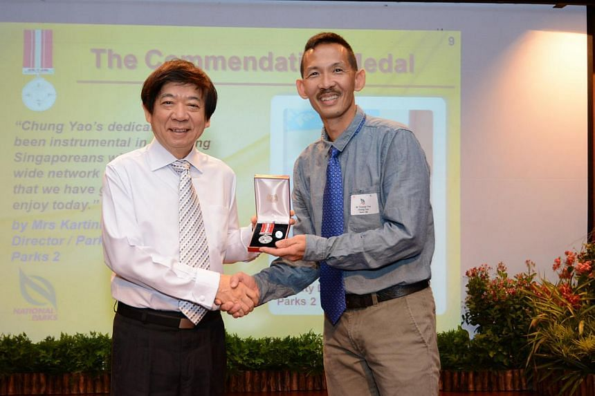 National Development Minister Khaw Boon Wan (left) presenting commendation medal to National Parks Board officer Thomas Yee Chung Yao at the ministry's National Day Awards investiture on Friday, Nov 11, 2014 at MND Auditorium at Maxwell Road. -- PHOT