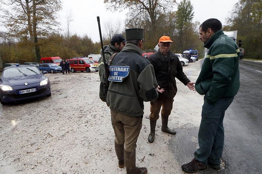 Members of the National Hunting and Wildlife Office talk on Nov 14, 2014 in the woods of Ferrieres-en-Brie, on the outskirts of Paris, during the ongoing search for what was first described as a tiger on the loose. French authorities said on Nov 14 t
