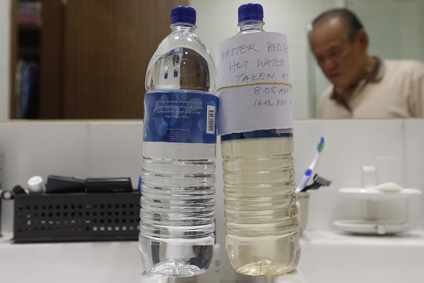 Retired trader Tong Chan Fui, 74, compares the bottle of rust-coloured water stored from the tap in his bedroom toilet with a clear one on 14 Nov 2014. -- ST PHOTO: KEVIN LIM