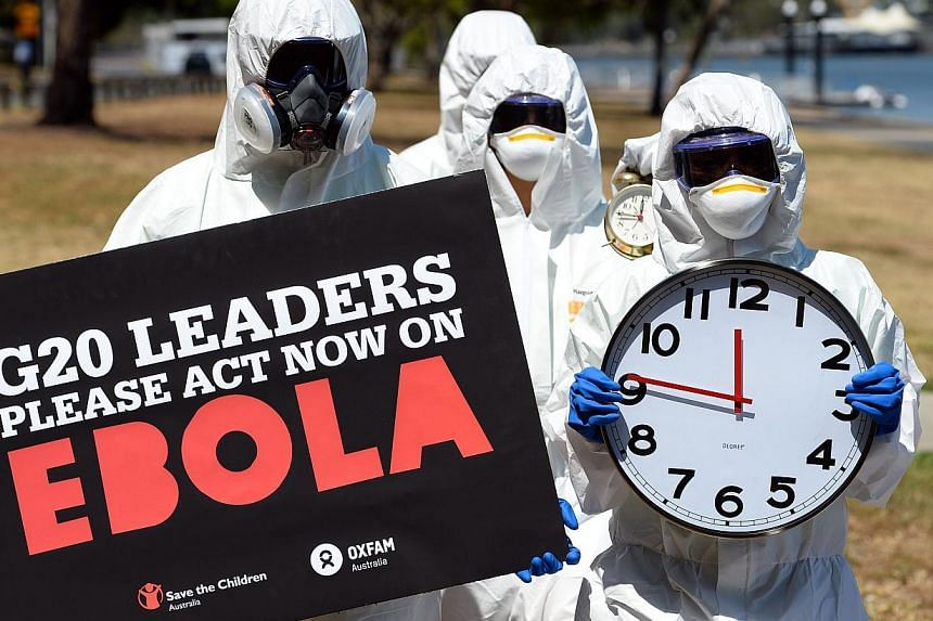 Protestors carry clocks to show timing is running out during an Ebola protest event in Brisbane on Nov 15, 2014. Several protests have been organised in connection with the G20 summit. -- PHOTO: AFP