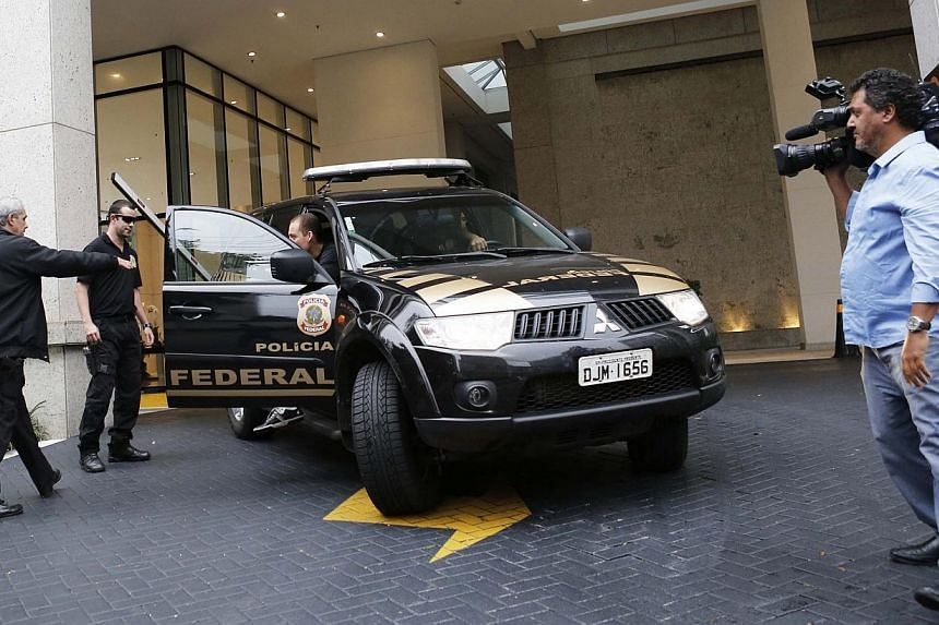 "Federal police enter a vehicle as they leave the headquarters of Brazilian conglomerate Camargo Correa during ""Operation Car Wash"" in Sao Paulo on Nov 14, 2014. Brazilian police arrested a former Petróleo Brasileiro SA executive on Friday, sending t"