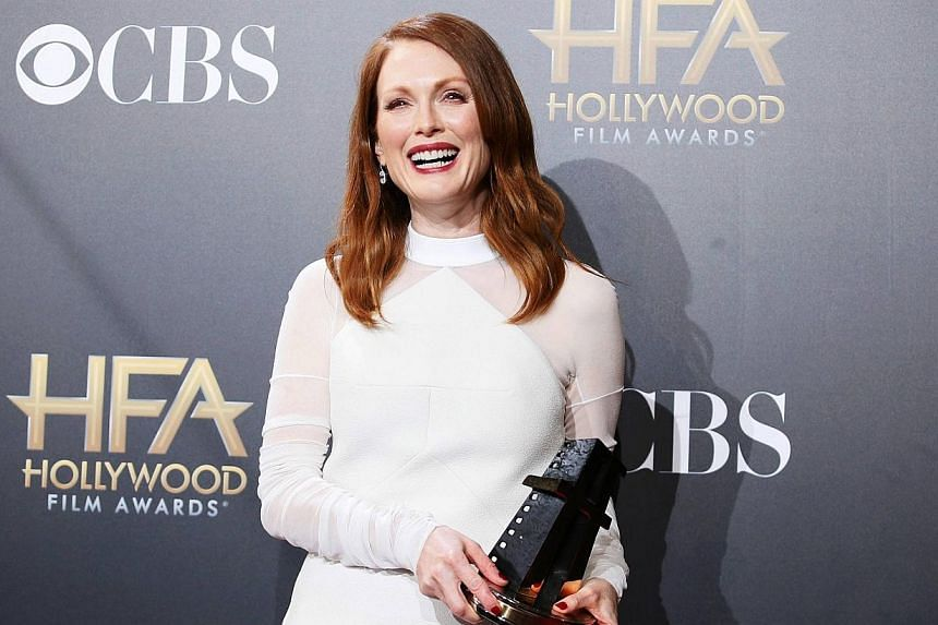 Actress Julianne Moore poses backstage with her actress award for Still Alice during the Hollywood Film Awards in Hollywood, California on Nov 14, 2014. -- PHOTO: REUTERS