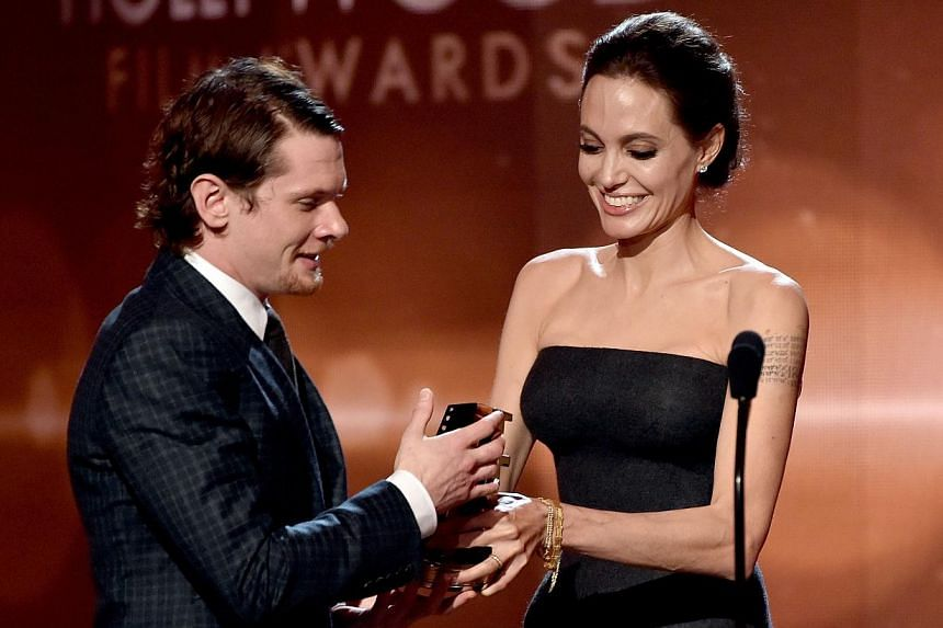Actor Jack O'Connell accepts the New Hollywood Award for Unbroken from actress Angelina Jolie onstage during the 18th Annual Hollywood Film Awards at The Palladium on Nov 14, 2014, in Hollywood, California. -- PHOTO: AFP