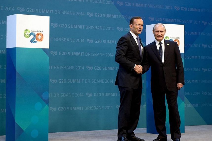 Russia's President Vladimir Putin (right) is welcomed by Australia's Prime Minister Tony Abbott upon his arrival for the G20 summit in Brisbane on Nov 15, 2014. -- PHOTO: REUTERS