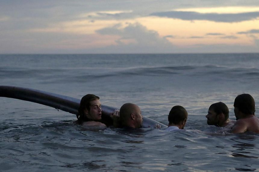 People try to help a stranded whale at Popoyo beach, 35km from Rivas, Nicaragua on Nov 14, 2014. -- PHOTO: AFP