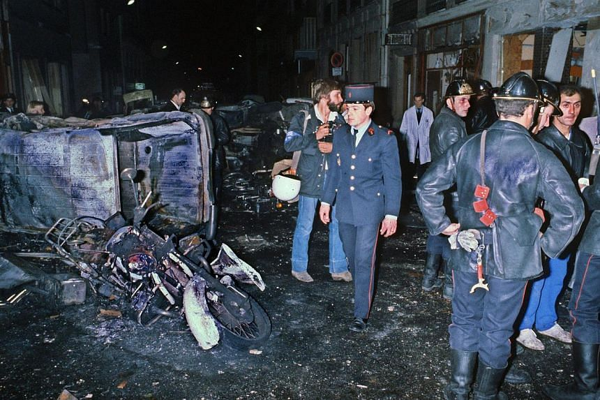 A file picture taken on Oct 3, 1980 shows firefighters standing by the wreckage of a car and motocycle after a bomb attack at a Paris synagogue on Rue Copernic which killed four people.A Canadian academic was charged on Saturday over the deadly
