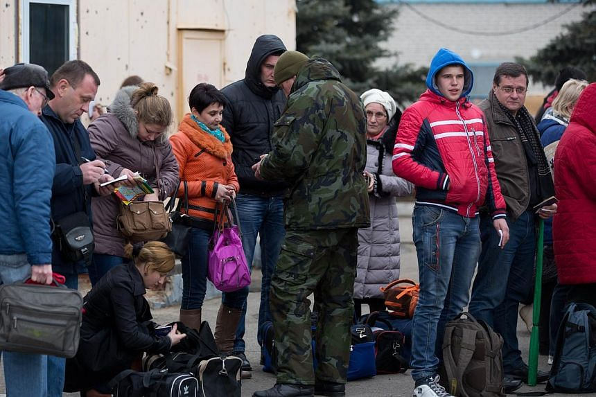 Border guards of the self-declared Donetsk People's Republic check passengers' IDs as they wait to cross from East Ukraine into Russia at the border crossing of Uspenka, on Nov 15 2014. Ukraine's President Petro Poroshenko issued a decree ordering th