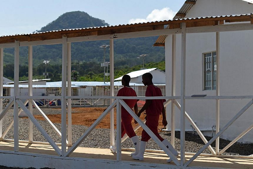 Health workers walk on Nov 13, 2014, on Kerry Town treatment centre, on the outskirts of Freetown, one of several installations built by the British government in Sierra Leone on a effort to fight the outbreak of Ebola. -- PHOTO: AFP