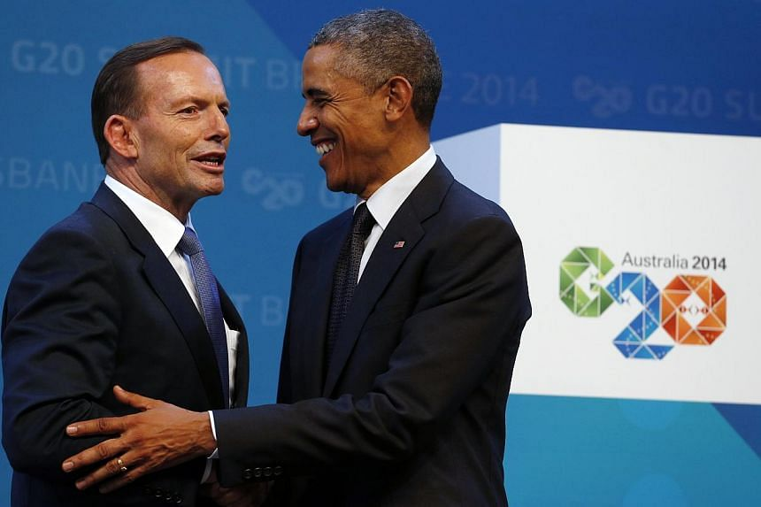 Australian Prime Minister Tony Abbott (left) reacts as he shakes hands with US President Barack Obama while officially welcoming leaders to the G20 summit in Brisbane, Australia on Nov 15, 2014. -- PHOTO: REUTERS