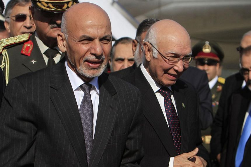 Afghan President Ashraf Ghani (left) walks with Sartaj Aziz, adviser on foreign affairs to Pakistan Prime Minister Nawaz Sharif, after arriving at Chaklala Airbase in Rawalpindi near Islamabad Nov 14, 2014. Ghani arrived in Islamabad on a two day off