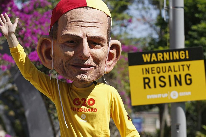 A protester, wearing a mask depicting Australian Prime Minister Tony Abbott, calls for global equality among nations outside the venue site of the annual Group of 20 leaders summit in Brisbane, Nov 14, 2014. G-20 leaders representing the bulk of the
