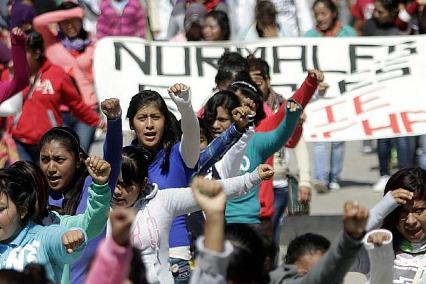 People take part in a protest to demand the safe return of 43 students who went missing in southern Mexico, after an attack by gang-linked police last Sept 26, in Chilpancingo, Guerrero state, Mexico on Nov 14, 2014. -- PHOTO: AFP