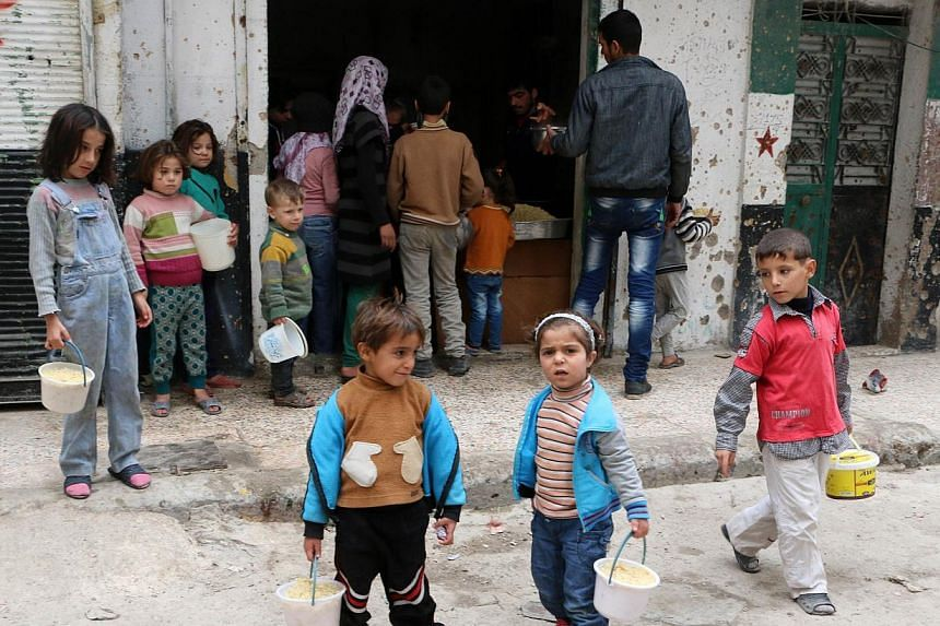 Syrian children stand outside a community kitchen that caters for impoverished families in the neighbourhood, after receiving their portion of food aid, in the Salhin district of the northern city of Aleppo on Nov 15, 2014. In the Syrian town of