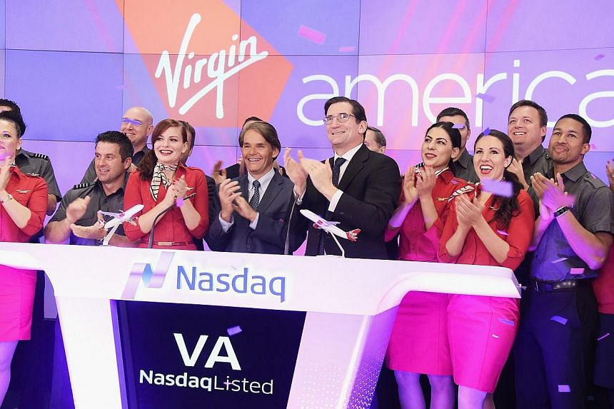 Virgin America president and CEO David Cush (centre) and Nasdaq CEO Robert Greifeld (right) ring the opening bell in celebration of the company's initial public offering on Nov 14, 2014 in New York City. -- PHOTO: AFP