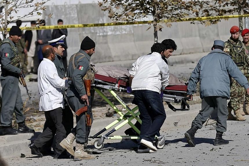 Officials carry a dead body on a stretcher at the site of a blast in Kabul on Nov 16, 2014. Shukria Barakzai, an outspoken Afghan female lawmaker, survived a suicide attack on her vehicle on Sunday but three civilian bystanders were killed, a police