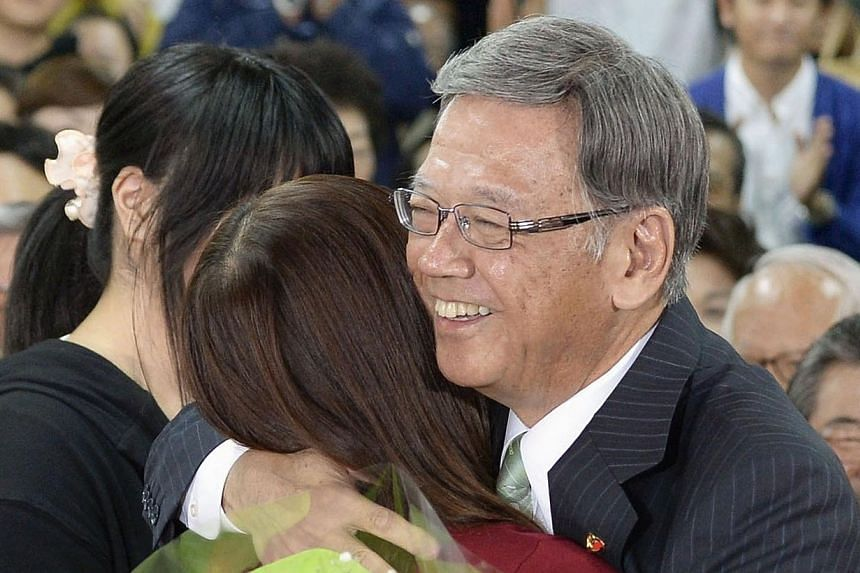 Former Naha mayor Takeshi Onaga, (right) hugs his daughter as they celebrate his victory in the Okinawa gubernatorial election in Naha, Okinawa on Nov 16, 2014.The election of Mr Onaga, who opposes plans to relocate a US military base within th